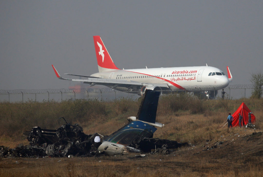 A plane lands near the crash site, a day after the US-Bangla airplane crashed while arriving from Dhaka, in Kathmandu, Nepal. Photo by Navesh Chitrakar/Reuters