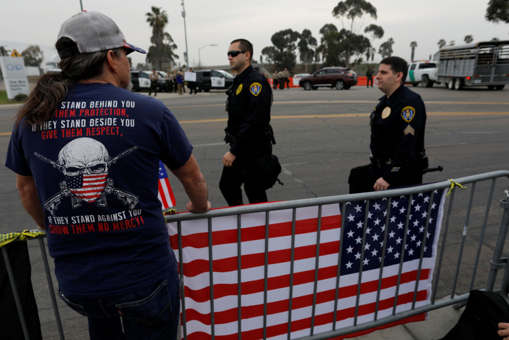 A pro-Trump supporter looks out behind a fence as a large police presence has closed off access near the border for the visit of President Donald to view border wall prototypes in San Diego, California. Photo by Mike Blake/Reuters