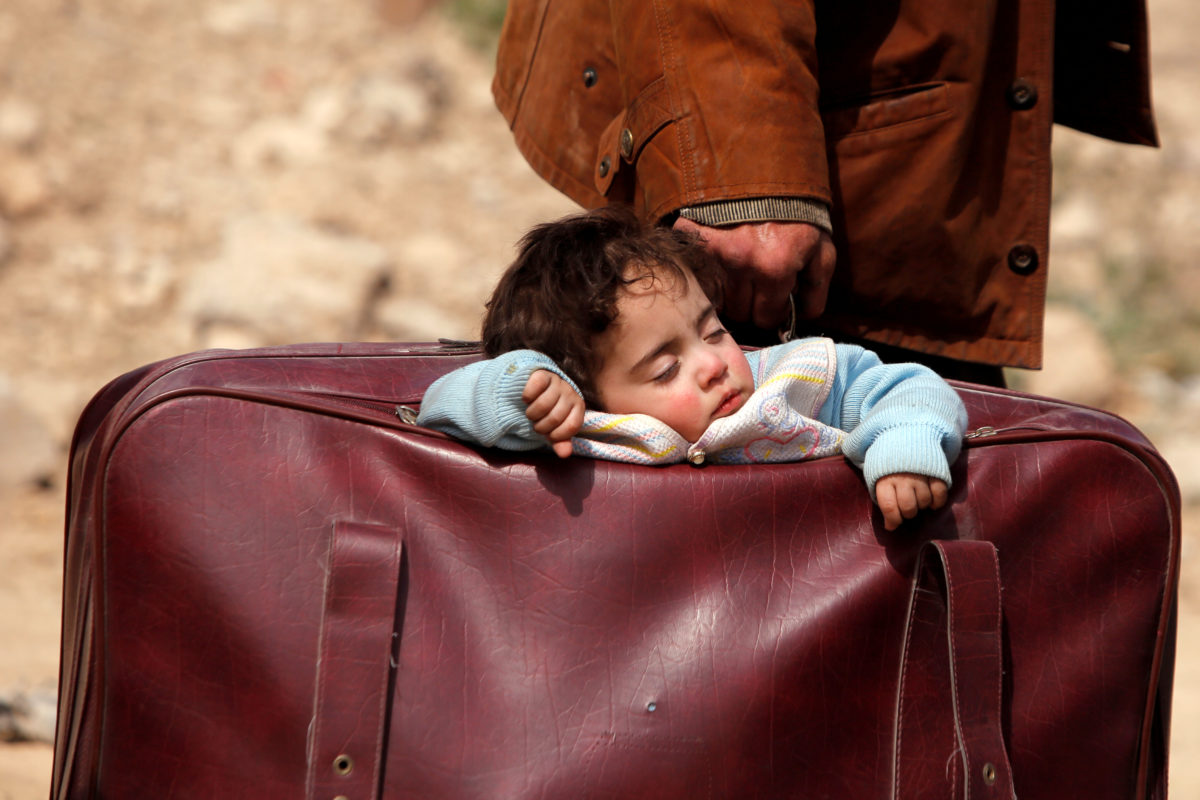 A child sleeps in a bag in the village of Beit Sawa, Eastern Ghouta, in Syria on March 15. Thousands are fleeing since aerial bombardments intensified. Photo by Omar Sanadiki/Reuters
