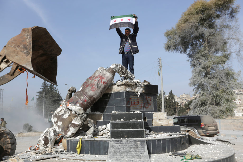Turkish-backed Free Syrian Army member holds a flag as they pull down Kurdish statue in the center of Afrin, Syria. Photo by Khalil Ashawi/Reuters