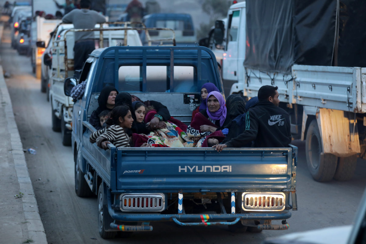 Kurdish civilians sit at the back of a truck in Afrin, Syria. Photo by Khalil Ashawi/Reuters