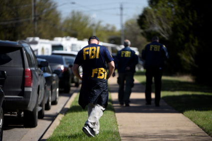 FBI agents walk towards a crime scene on Mission Oaks Boulevard following an explosion in Austin, Texas. Photo by Sergio Flores/Reuters