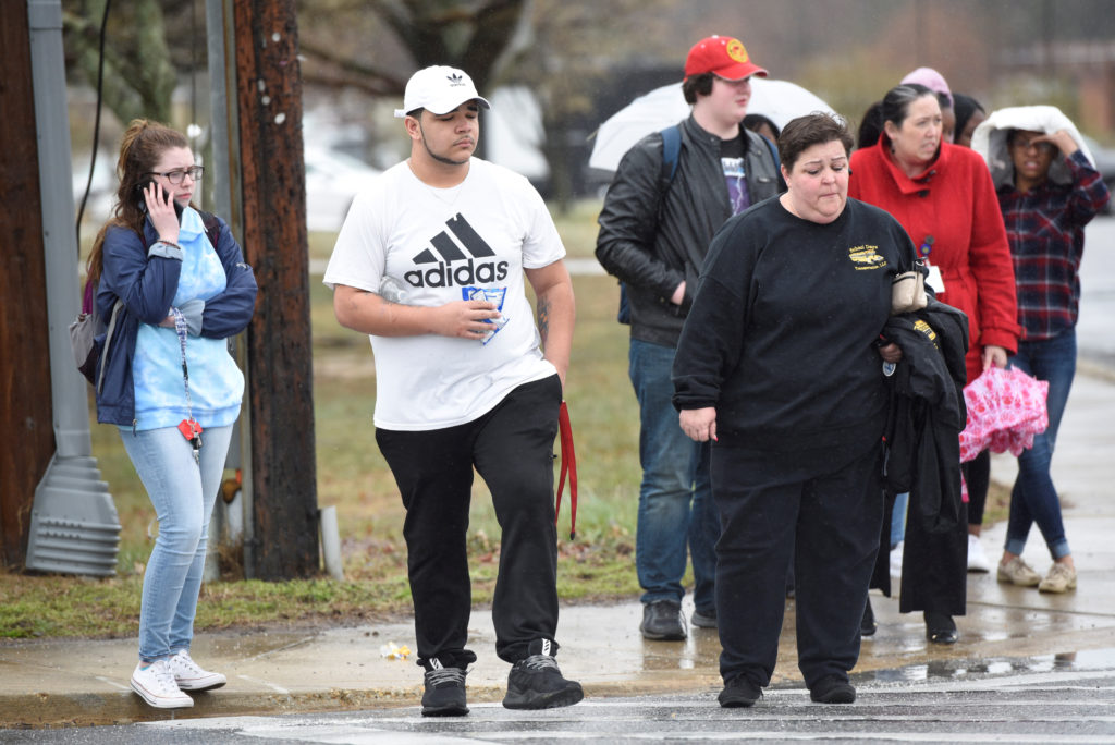 Great Mills High School senior Wayne Waul (2nd L) and his mother Jill Ryan (4th L) leave Leonardtown High School in Leonardtown, Maryland, U.S., March 20, 2018. Great Mills students and parents reunited at Lenoardtown after the shooting at their school. REUTERS/Sait Serkan Gurbuz - RC1739F4D140