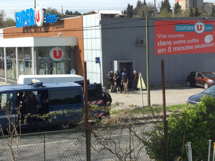 Police are seen at the scene of a hostage situation in a supermarket in Trebes, France, in this picture obtained from a social media video. Photo by La Vie a Trebes via Reuters