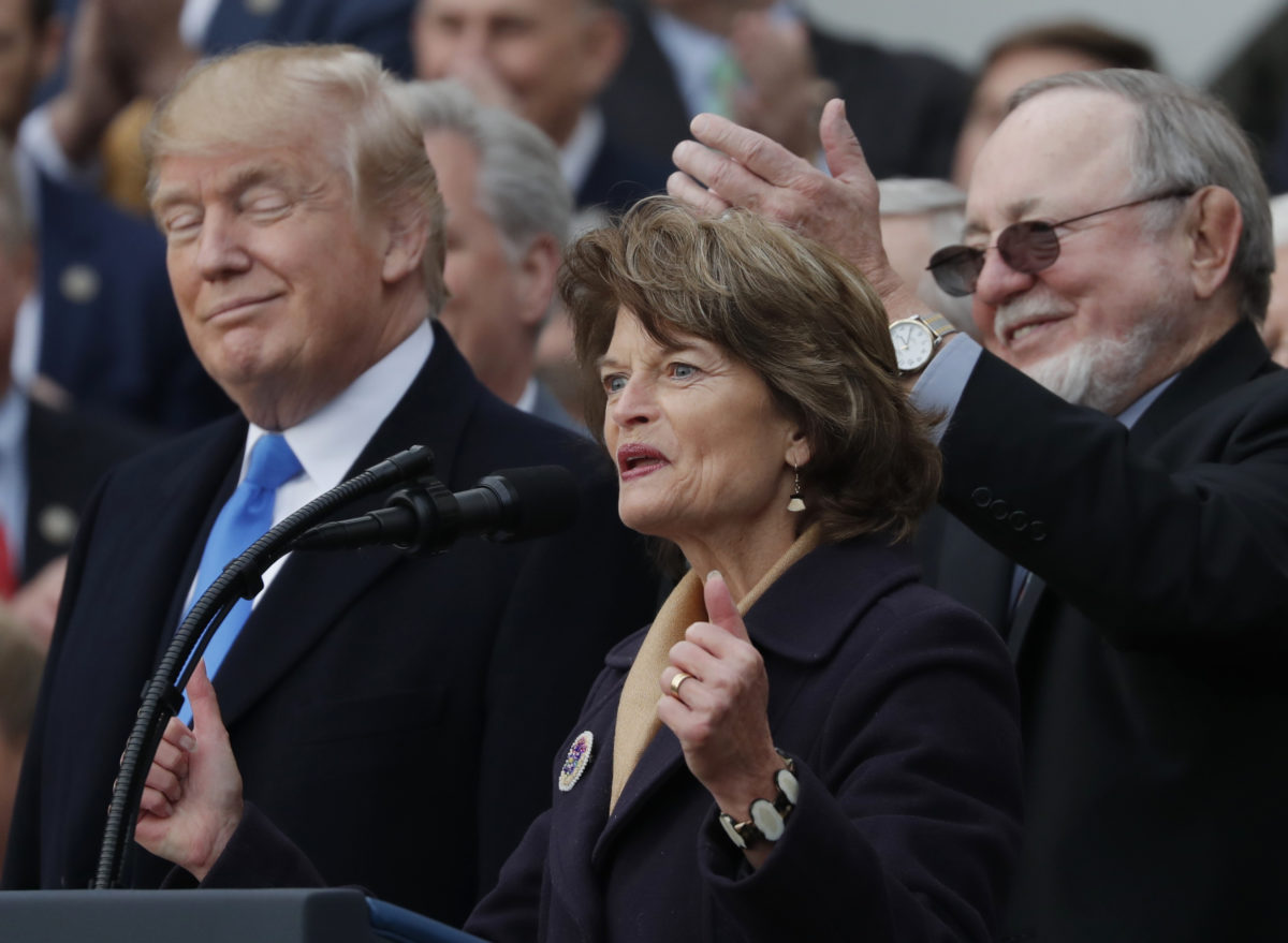 U.S. President Donald Trump stands with with Alaska's Sen. Lisa Murkowski (R-AK), and Rep Don Young (R-AK) as he celebrates with Congressional Republicans after the U.S. Congress passed sweeping tax overhaul legislation on the South Lawn of the White House in Washington, U.S., December 20, 2017. REUTERS/Carlos Barria - HP1EDCK1N054O