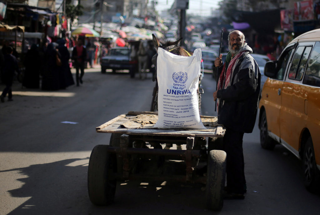 A Palestinian man stands next to a cart carrying a flour sack distributed by the United Nations Relief and Works Agency (UNRWA) in Khan Younis refugee camp in the southern Gaza Strip. Photo by Ibraheem Abu Mustafa/Reuters