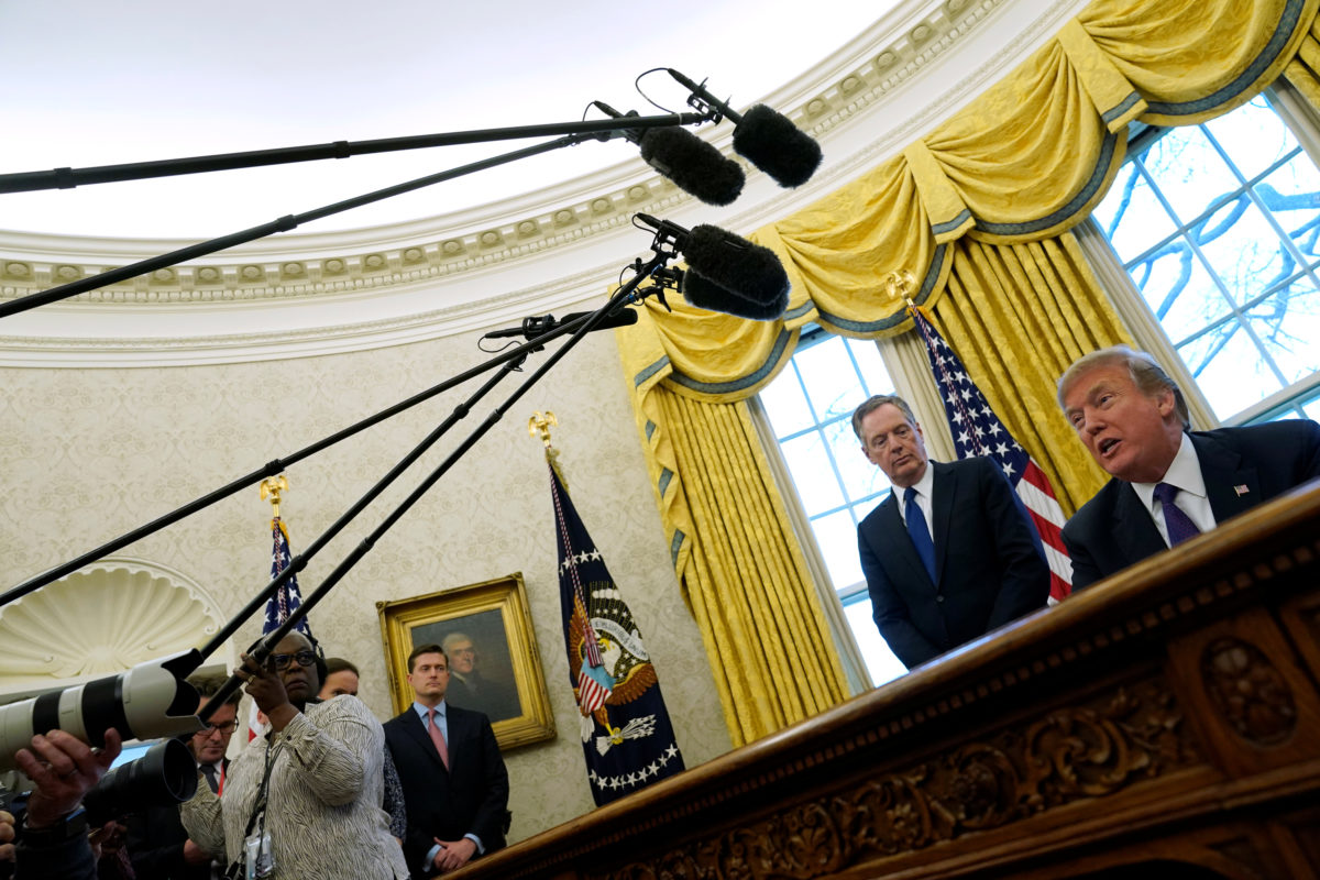 Trade Representative Robert Lighthizer stands behind President Donald Trump as Trump prepares to sign directives to impose tariffs on imported washing machines and solar panels in the Oval Office at the White House in Washington, D.C. Photo by Jonathan Ernst/Reuters