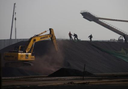 FILE PHOTO: Workers work on a pile of iron ore at a steel factory in Tangshan, Hebei province, China November 3, 2015. REUTERS/Kim Kyung-Hoon/File Photo - RC18ECDC6D40