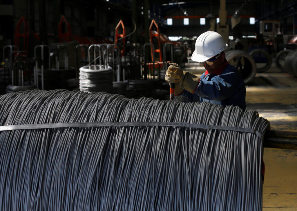 FILE PHOTO: Worker inspects wire rod at TIM stainless steel wire factory in Huamantla
