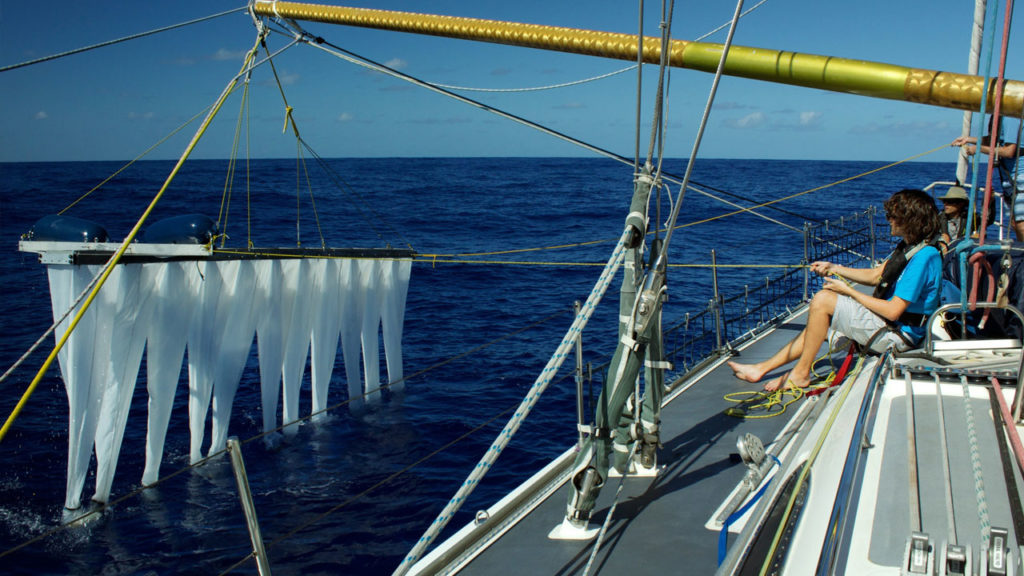 A scientist lowers a multi-level-trawl into the ocean. Photo by The Ocean Cleanup