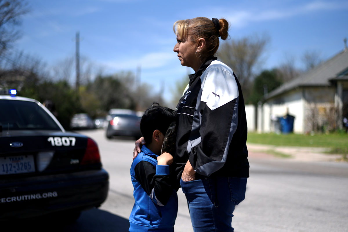 Isaac Machado hides behind his hat against his mother Delores just outside the scene of an explosion on Galindo Street in Austin, Texas, U.S., March 12, 2018. REUTERS/Sergio Flores - RC19E5318870