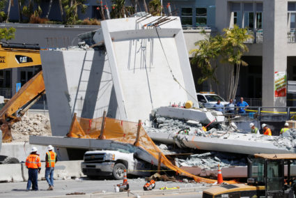 Workers remove debris from a collapsed pedestrian bridge at Florida International University in Miami, Florida, U.S., March 16, 2018. REUTERS/Joe Skipper - RC1F4AABCED0