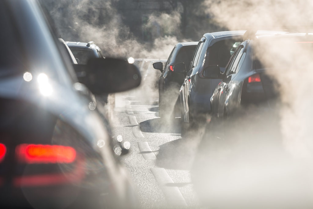 Blurred silhouettes of cars surrounded by steam from the exhaust pipes. Traffic jam. Photo by elcovalana/via Adobe