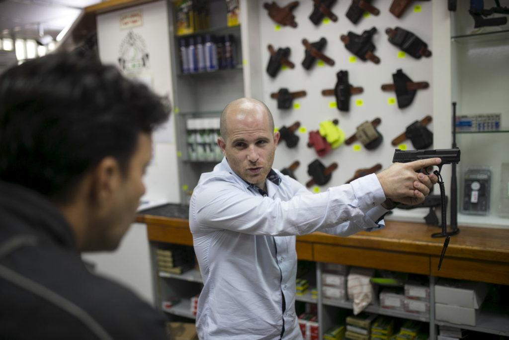 A salesman shows a pistol to a customer at a gun shop REUTERS/Baz Ratner - GF20000025409