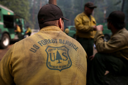 GROVELAND, CA - AUGUST 25: U.S. Forest Service firefighters take a break from battling the Rim Fire at Camp Mather on August 25, 2013 near Groveland, California. The Rim Fire continues to burn out of control and threatens 4,500 homes outside of Yosemite National Park. Over 2,000 firefighters are battling the blaze that has entered a section of Yosemite National Park and is currently 7 percent contained. (Photo by Justin Sullivan/Getty Images)