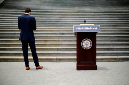 "A staff stands next to a podium which reads ""#NoBillNoBreak"" prior to a news conference by U.S. House Minority Leader Nancy Pelosi (D-CA) (not pictured) to call on House Speaker Paul Ryan to allow a vote on gun violence prevention legislation in Capitol Hill, Washington, U.S., June 22, 2016. REUTERS/Carlos Barria/File Photo - TM3ECB80OSC01"
