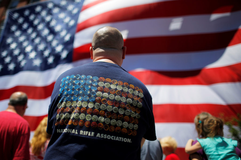 Onlookers, including a man wearing a National Rifle Association (NRA) t-shirt, watch as a 95-by-50-foot American flag is u...
