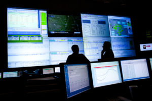 Reliability Coordinators Wes Watkins (L) and Kim Engram (R) monitor the state power grid during a tour of the Electric Reliability Council of Texas (ERCOT) command center in Taylor, Texas August 14, 2012. The crisis facing Texas, and indeed large swathes of the U.S. economy that depend on seven regional grid operators to keep their delicate electricity systems in balance, has been years in the making as cheap natural gas and new environmental rules force the closure of dozens of older coal-fired units and deter the construction of new ones, while consumption steadily rises. REUTERS/Julia Robinson (UNITED STATES - Tags: ENERGY BUSINESS) - TM3E88E1PYX01
