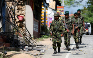 Sri Lanka's Special Task Force soldiers walk past a damaged houses after a clash between two communities in Digana central district of Kandy, Sri Lanka March 8, 2018. REUTERS/Dinuka Liyanawatte - RC174D426FC0