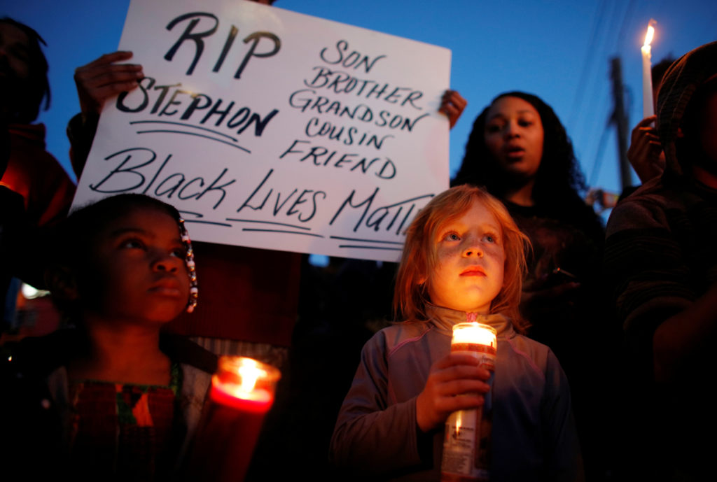 Katelyn Camero (R) and Amia Levi hold candles during a vigil to protest the police shooting of Stephon Clark, in Sacramento, California, U.S. March 23, 2018.  REUTERS/Bob Strong - RC1223EB92C0