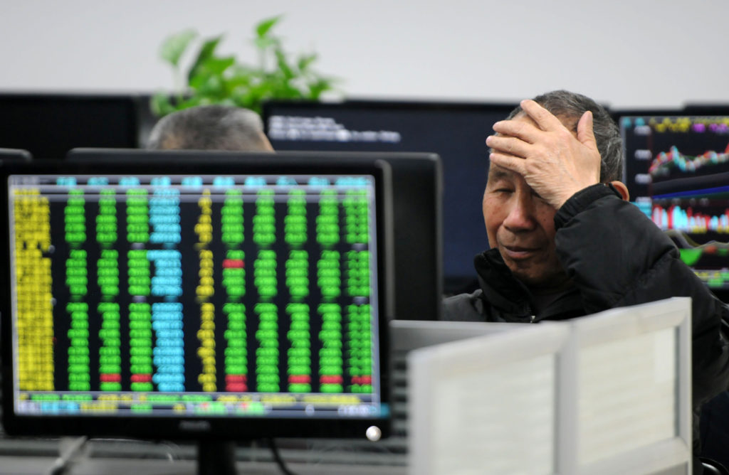 A man looks at a monitor showing stock information at a brokerage house in Jiujiang, Jiangxi province, China March 23, 2018. Photo by China Daily via REUTERS