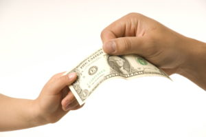close-up adult hand taking dollar bill from child's hand (Photo by: Digital Light Source/UIG via Getty Images)