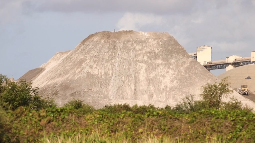 Puerto Ricans in Guayama say particles from this 120-foot high mound of coal ash mixed with water covers their homes and may be the cause of elevated public health issues. Photo by PBS NewsHour Weekend