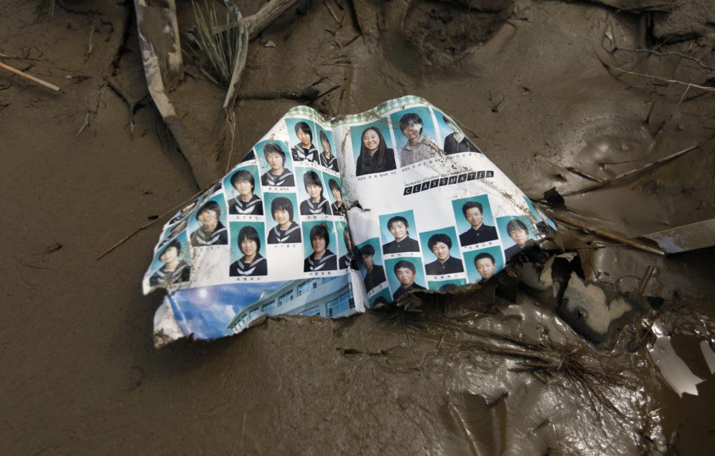 A torn page with headshots of students from a class photo album lies on mud outside the tsunami-hit Okawa Elementary School in Ishinomaki, Miyagi Prefecture, northeastern Japan March 29, 2011. Photo by Yuriko Nakao/Reuters