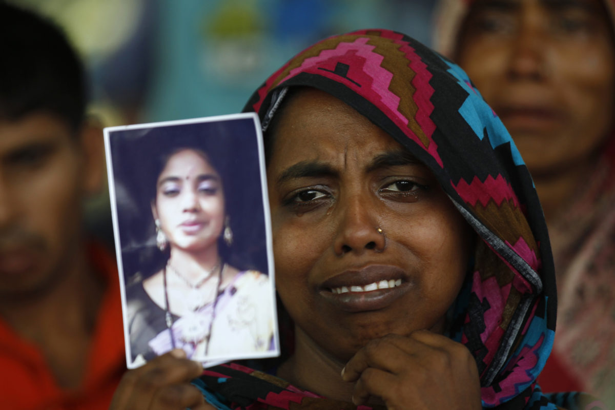 A woman holds a picture of her relative, a garment worker who went missing in the Rana Plaza collapse in Savar, Bangladesh, a year after the accident on April 24, 2014. Photo by Andrew Biraj/Reuters