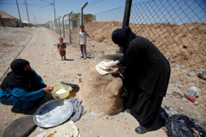Displaced Iraqi women from Tal Afar make bread in Salamya camp, east of Mosul, Iraq on Aug. 6, 2017. Photo by Khalid Al-Mousily/Reuters
