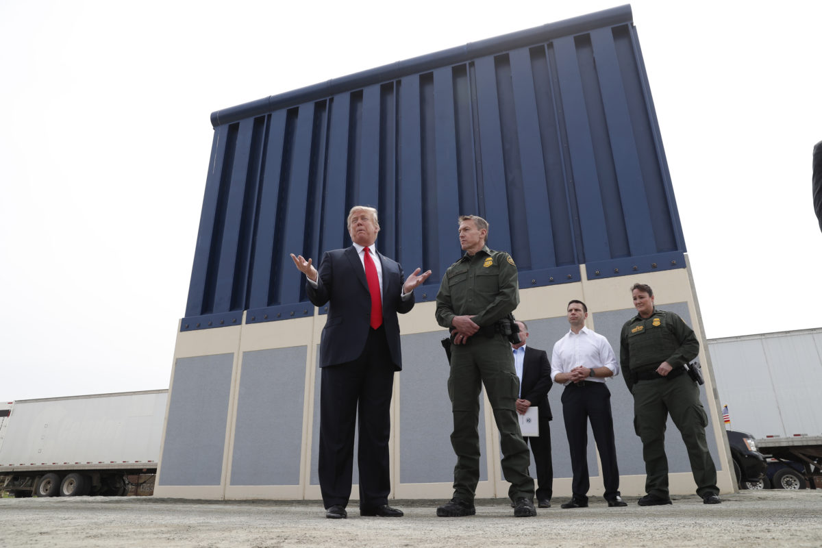 President Donald Trump talks with a U.S. Customs and Border Protection (CBP) Border Patrol Agent while participating in a tour of U.S.-Mexico border wall prototypes near the Otay Mesa Port of Entry in San Diego, California. Photo by Kevin Lamarque/Reuters