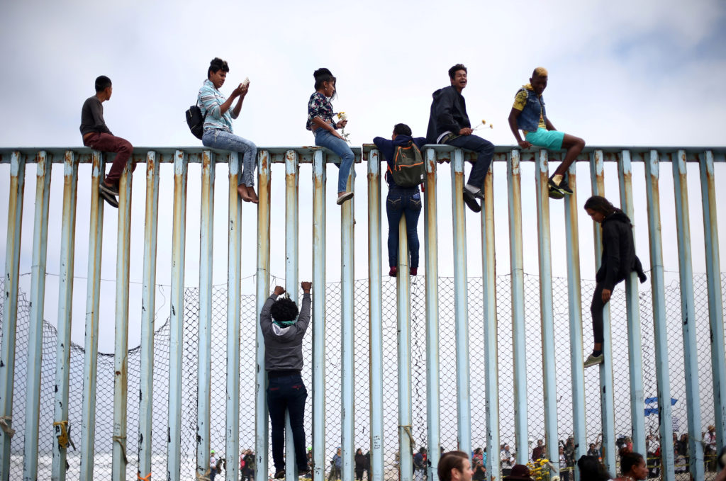 Members of a caravan of migrants from Central America climb up the border fence between Mexico and the U.S., as a part of a demonstration prior to preparations for an asylum request in the U.S., in Tijuana, Mexico April 29, 2018. Photo by Edgard Garrido/Reuters