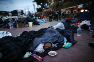Members of a caravan of migrants from Central America sleep near the San Ysidro checkpoint after a small group of fellow migrants entered the United States border and customs facility, where they are expected to apply for asylum, in Tijuana, Mexico April 30, 2018. Photo by Edgard Garrido/Reuters