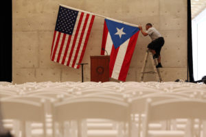A worker takes down U.S and Puerto Rican flags after a 2016 rally of then-Democratic presidential candidate Bernie Sanders in San Juan, Puerto Rico. Photo by Alvin Baez/Reuters