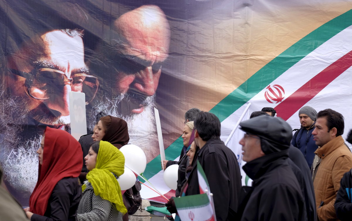 People walk past images of the late leader of the Islamic Revolution Ayatollah Ruhollah Khomeini (right) and Iran's Supreme Leader Ayatollah Ali Khamenei, during a ceremony marking the 37th anniversary of the Islamic Revolution, in Tehran on Feb. 11, 2016. File photo by Raheb Homavandi/TIMA via Reuters