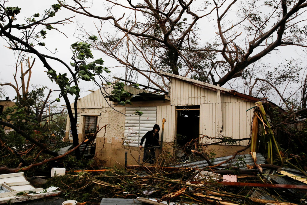 A man looks for valuables in the damaged house of a relative after the area was hit by Hurricane Maria in Guayama