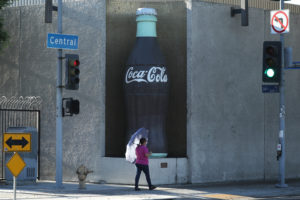 A woman walks past the Coca Cola bottling plant in Los Angeles, California, U.S. October 24, 2017. REUTERS/Lucy Nicholson - RC1FDEE94050