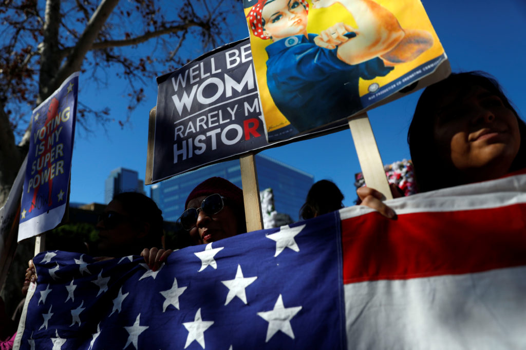 People hold an American flag during the second annual Women's March in Los Angeles, California, U.S. January 20, 2018. REU...