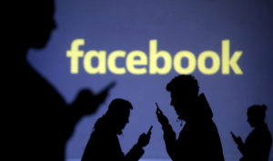 Silhouettes of mobile users are seen next to a screen projection of the Facebook logo in this picture illustration. File photo by Dado Ruvic/Illustration/Reuters