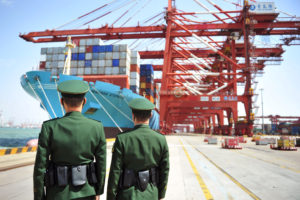 Police officers are seen in front of a cargo ship with containers at a port in Qingdao, Shandong province, China April 6, 2018. Photo by Reuters
