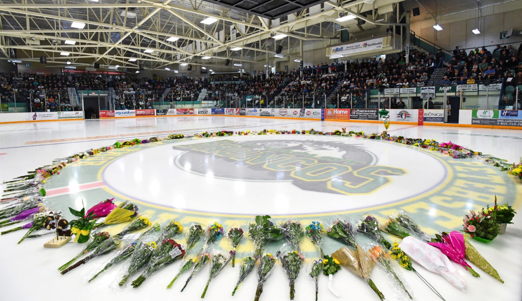 Flowers lie at center ice as people gather for a vigil at the Elgar Petersen Arena, home of the Humboldt Broncos, to honor the victims of a fatal bus accident in Humboldt, Saskatchewan, Canada. Photo by Jonathan Hayward/Pool via Reuters