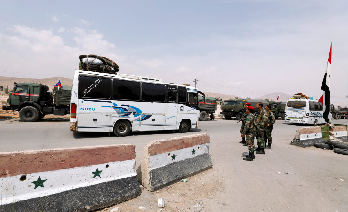 A bus carries rebels and their families who left Douma, at the entrance of the Wafideen camp in Damascus, Syria. Photo by Omar Sanadiki/Reuters