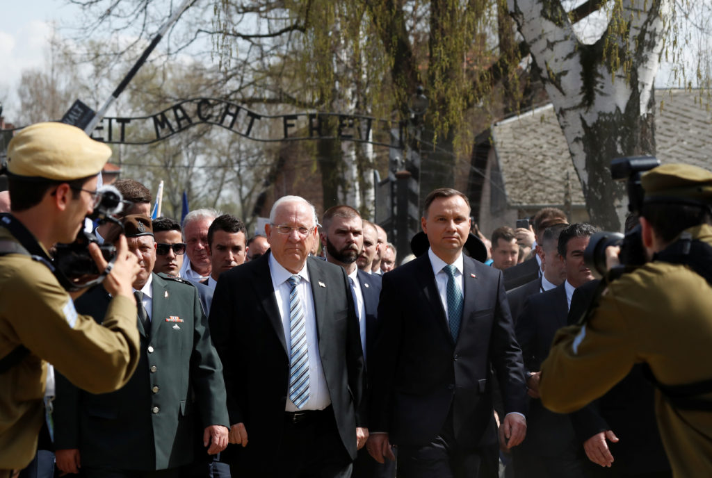 "Polish President Andrzej Duda and Israeli President Reuven Rivlin are seen in front of the ""Arbeit macht frei"" (Work sets you free) gate as they take part in the annual ""March of the Living"" to commemorate the Holocaust at the former Nazi death camp Auschwitz, in Oswiecim, Poland, April 12, 2018. REUTERS/Kacper Pempel - RC1EB00DCD80"
