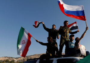 Syrians wave Iranian, Russian and Syrian flags during a protest against U.S.-led air strikes in Damascus on April 14. Photo by Omar Sanadiki/Reuters