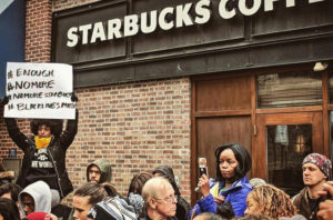 Tsehaitu Abye holds up a banner as people demonstrate outside a Starbucks cafe in Philadelphia, Pennsylvania, in this picture obtained from social media. Photo by @JILLIANPHL/Twitter via Reuters