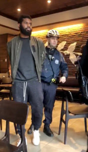 Police officers detain a man inside a Starbucks cafe in Philadelphia, Pennsylvania, in this picture grab obtained from social media video. Picture taken April 12, 2018. Photo by Melissa Depino via Reuters