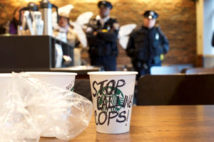 "A Starbucks coffee cup with ""Stop Calling Cops!"" written on the side sits on a table as police monitor protesters demonstrating inside a Center City Starbucks, where two black men were arrested, in Philadelphia, Pennsylvania. Photo by Mark Makela/Reuters"