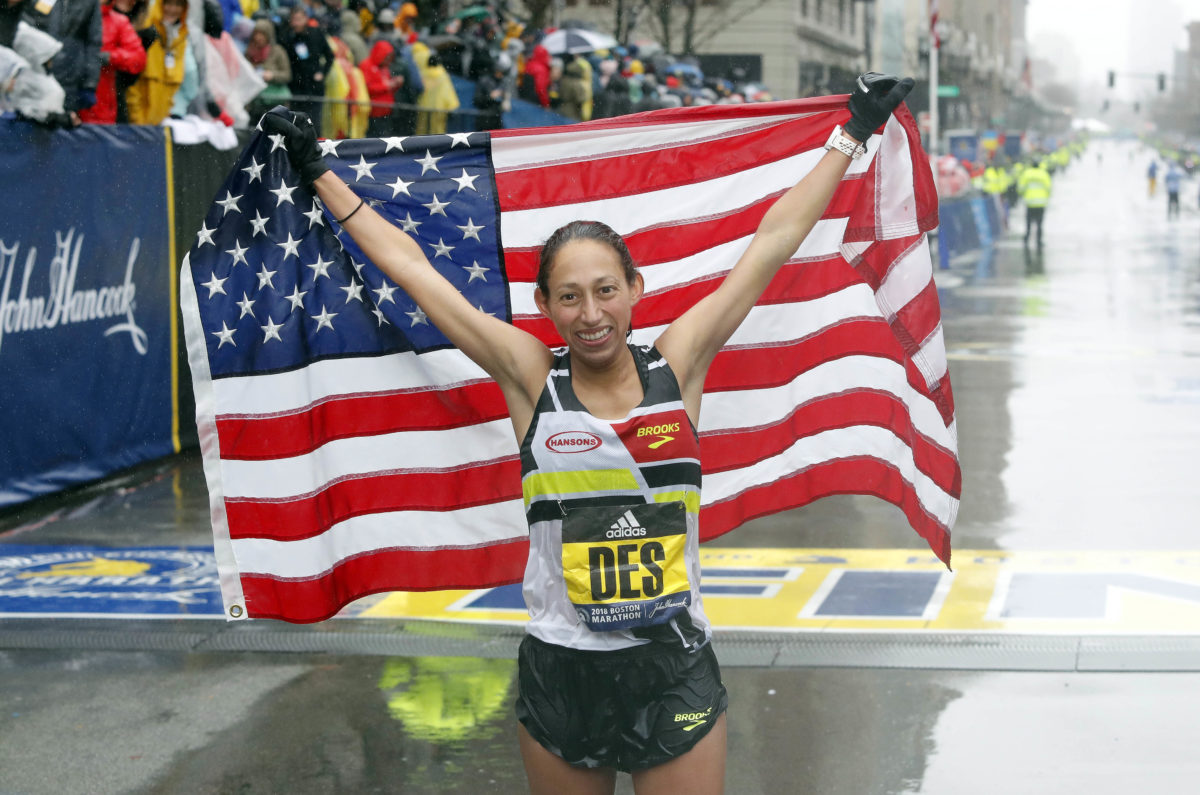 Desiree Linden of the USA holds up the American flag after winning the Women's Division of the 2018 Boston Marathon. Photo by Winslow Townson/USA TODAY Sports