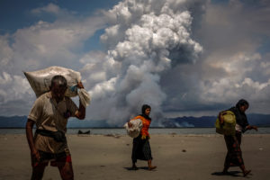 Smoke is seen on the Myanmar border as Rohingya refugees walk on the shore after crossing the Bangladesh-Myanmar border by boat through the Bay of Bengal, in Shah Porir Dwip, Bangladesh. Photo by Danish Siddiqui/Reuters