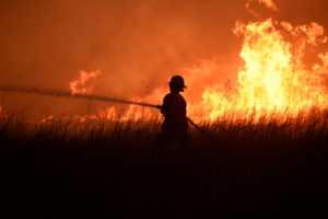 A firefighter works to control the Rhea fire near Seiling, Oklahoma, U.S. April 17, 2018. REUTERS/Nick Oxford,